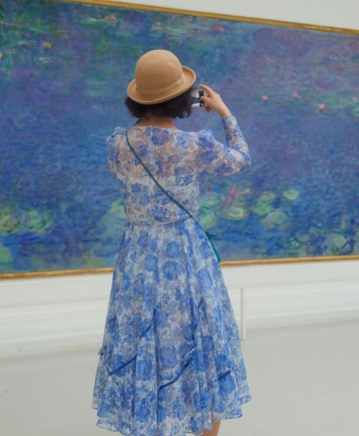 Woman with blue flowy floral dress standing in front of impressionist artwork with same colors.