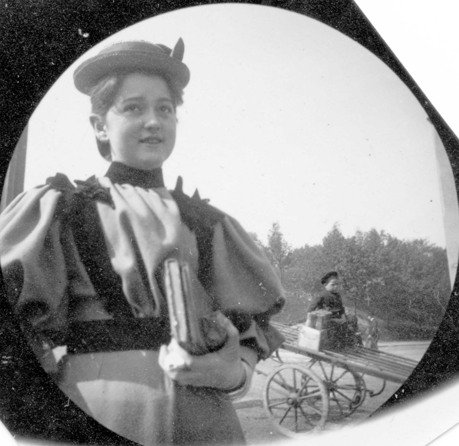 Girl in fancy hat & long dress carrying book with boy on a tipped cart in the background.