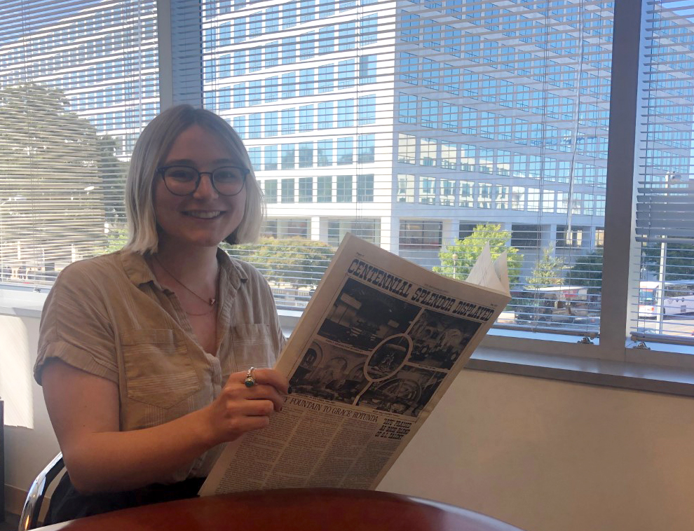 A person sits at a tables holding up a newspaper.