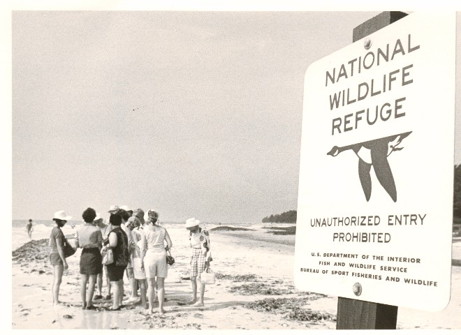 "View of a sign on a beach that reads: ""National Wildlife Refuge/Unauthorized Entry Prohibited/U.S. D"