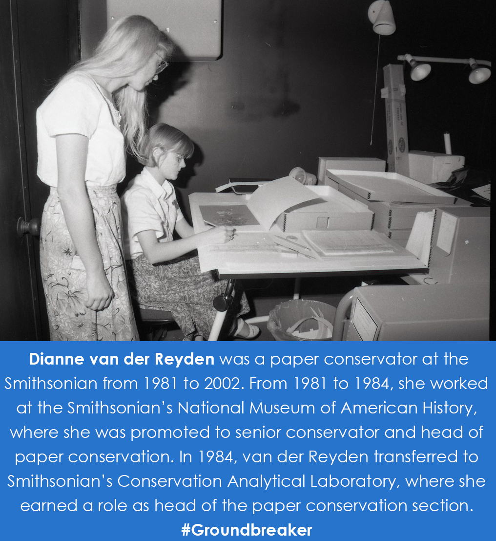 Van der Van der Reyden stands behind a conservator working on a document at a desk.