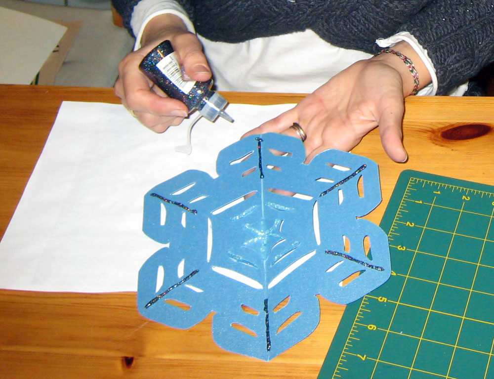 <p>Decorating tree-topper snowflake with glue glitter. </p>
