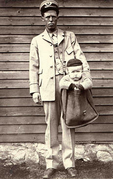Uniformed Letter Carrier with Child in Mailbag, Unidentified photographer