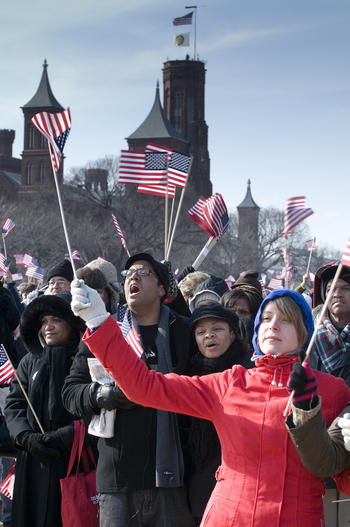 Inauguration visitors holding American flags in front of the Smithsonian Castle, January 20, 2009, b