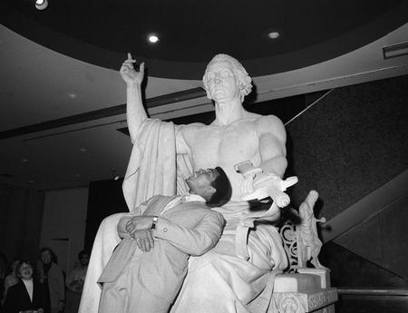 Muhammad Ali poses with the Horatio Greenough statue of George Washington.