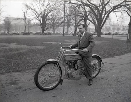 National Air Museum curator Paul Garber on a 1913 Harley Davidson motorcycle.