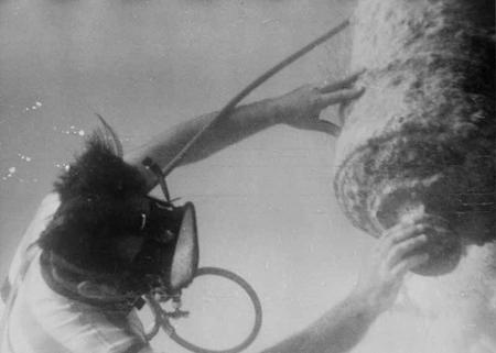 A diver examines a cannon underwater.