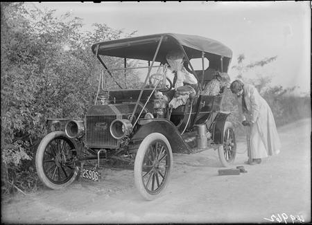 An unidentified woman uses a hand pump to fill the rear tire of a Ford Model T.