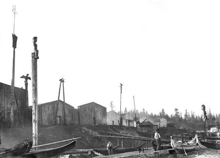 Shore lined with wooden houses, totem poles, and canoes.