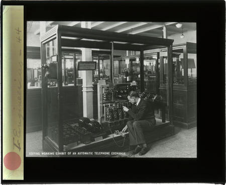A staff member tests a working exhibit of an automatic telephone exchange.