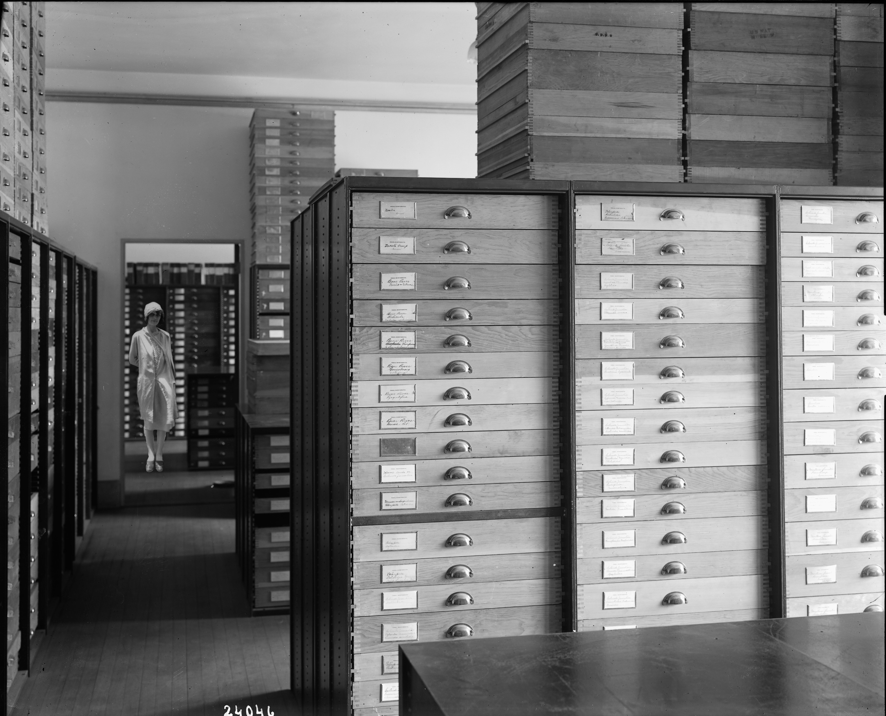 A woman stands in the doorway of an archival storage space. Labeled storage cabinets are in the room