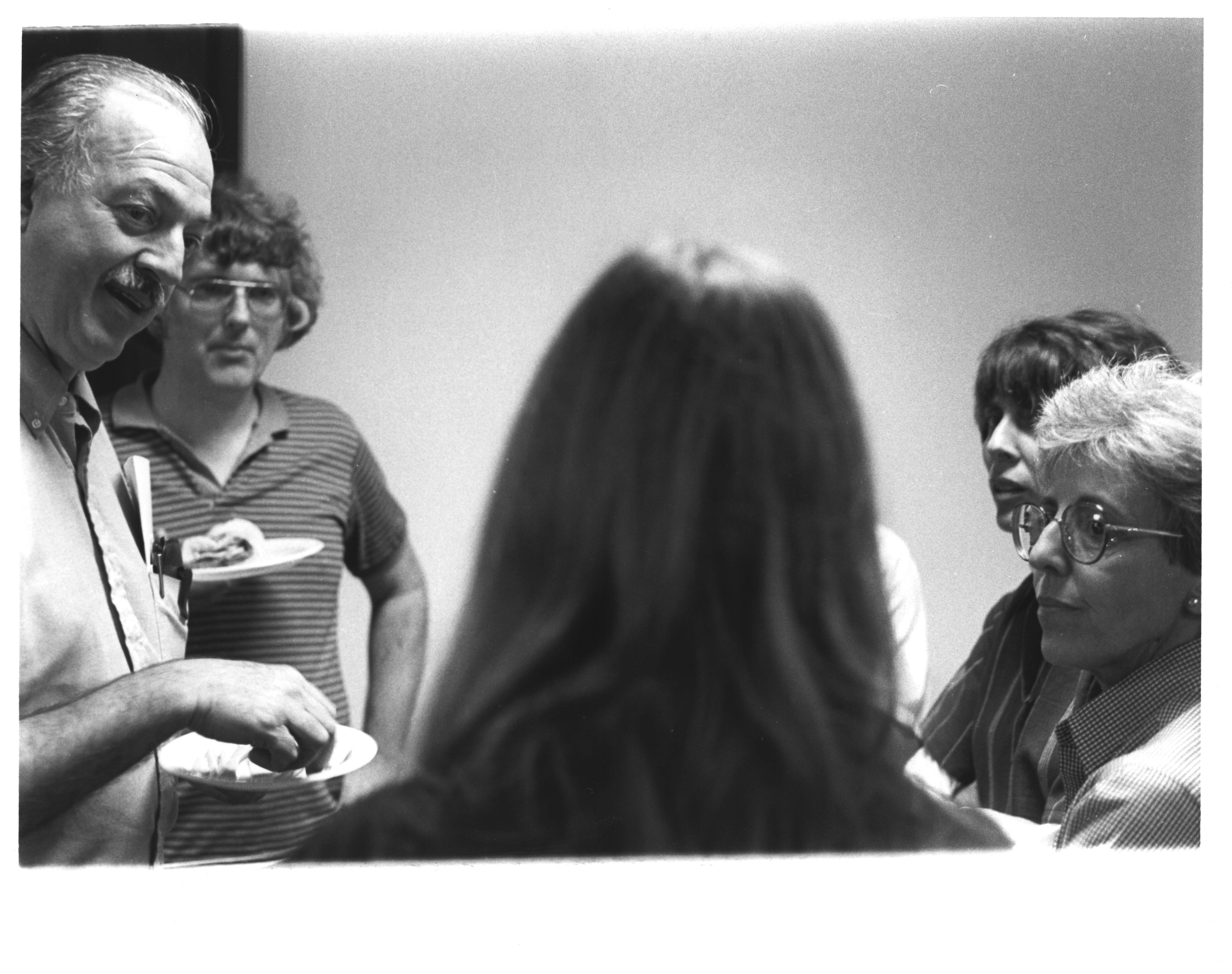Olga Linares stands on the right in a group mid discussion at the Naos Laboratory with Secretary Rob