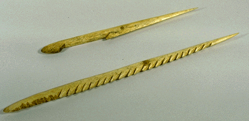 Two bone points of fishing spears, with notches in one