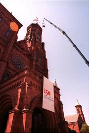 Images shows the a bell, made for the Smithsonian Institution's 150th anniversary, being hoisted to