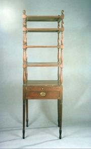 tall piece of wooden furniture, much like a side table with four wooden trays on top, each tray gett