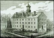 Five story symmetrical college building with four chimneys, a cupola on top and a front year with a