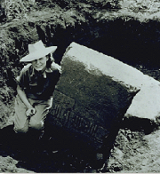 Photo of Marion Stirling next to an artifact that is being excavated