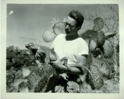 Photo of Schmitt holding an iguana with a cactus in the background