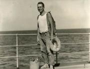 Black and white image of man standing on boat with ocean in the background.