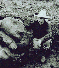 Black and white photo of Stirling sitting next to a rock during one of his archaeological digs