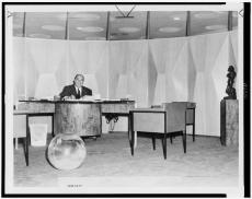 "William Zeckendorf sits behind desk in his ""cylindrical office"" in New York City; World-Telegram pho"