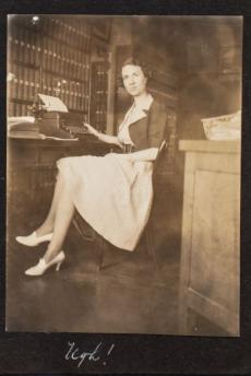 Young woman sitting at desk in office looking at the camera