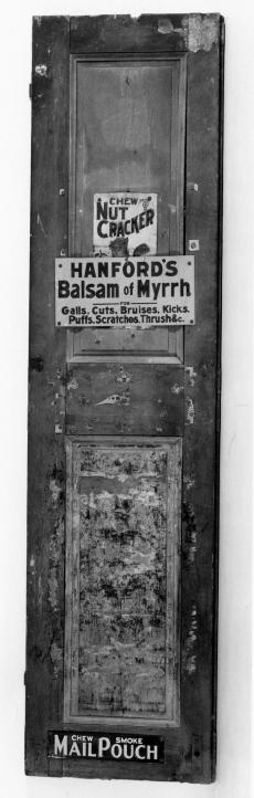 """Shutter with three signs on it. The signs read: """"Chew Nut Cracker,"""" """"Hanford's Balsam of Myrrh,"""" and"""