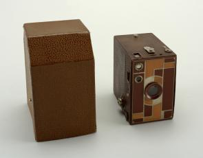 Color image of a Beau Brownie handheld box shaped camera, next to its light brown leather case