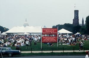 Image shows a crowded National Mall in Washington, D.C., for the Festival of American Folklife, with