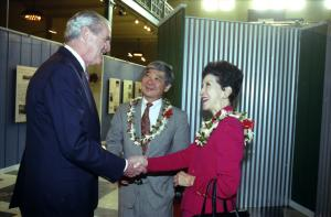 Color image of three people indoors, two of which are wearing leis and one is shaking the hand of an