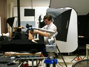 Person surrounded by photographic equipment.