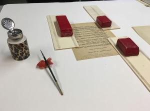 Archival document held by weights with artist brush nearby.