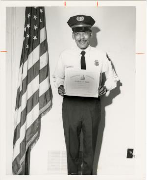 A guard in uniform smiles at the camera and holds up a certificate. He is standing next to an Americ