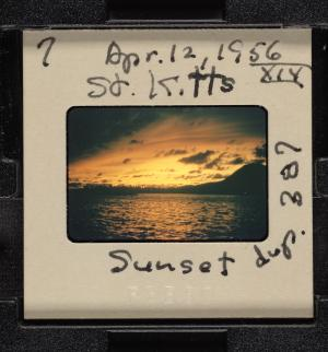 Film of sunset over water with white cardboard frame.
