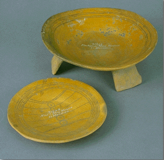 Two gold-colored, ceramic plates, one on a tripod, one at ground level