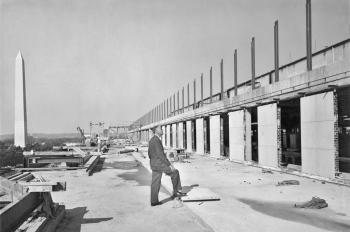 Frank A. Taylor standing on the fifth floor terrace and checking progress on construction of the Nat