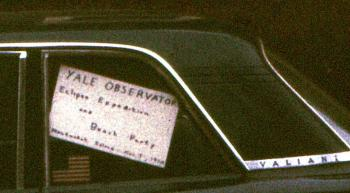 Sign for the Yale Observatory Eclipse Expedition and Beach Party, 1970, in a car window.