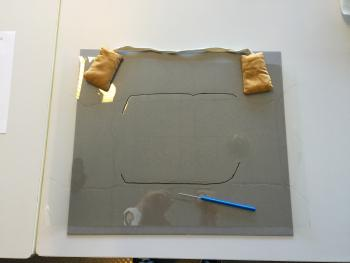 Transferring the outline of the photograph to the top layer of the base to create a snug fit. Photo
