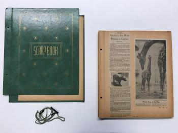 Green book cover with gold writing and page with newspaper clippings.