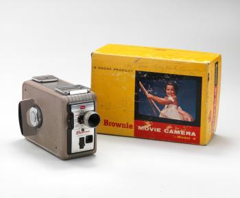Color image of a vintage Kodak Brownie video camera, next to a bright yellow packaging box