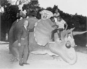 Black and white photograph of man standing next to sculpture of Triceratops with several young child
