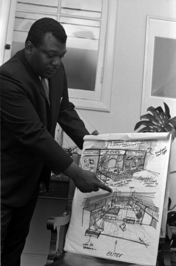 Black and white photograph of man pointing at concept drawing.