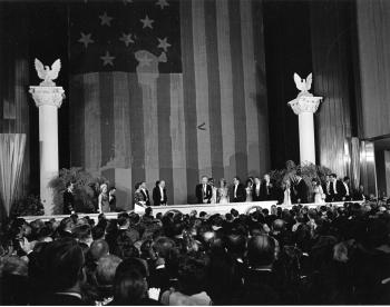 Guests standing in front of the Star-Spangled Banner at President Nixon's Inaugural Ball.