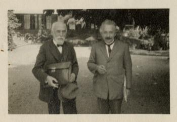 Black and white, slightly out of focus photograph of Lorentz and Einstein standing side by side out