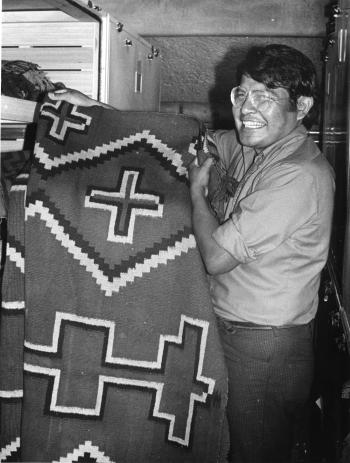 Black and white image of Harry Walters, Navajo male, holding a blanket in a museum collection storag