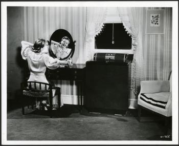 An advertisement showing a woman enjoying the cool of a General Electric home air conditioning unit,