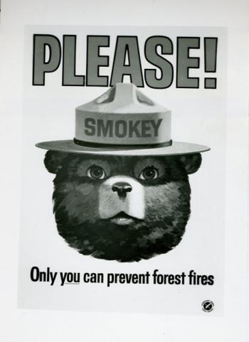 Scan of a black and white forest fire prevention poster featuring the head of Smokey the Bear