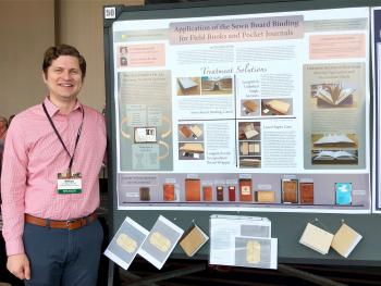 Color image of a man in a pink button down shirt standing next to a poster board presentation.