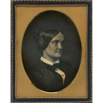 Black and white half-plate daguerreotype of a woman seen from the chest up, image is in a black fram
