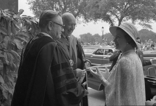 Two men in robes and a woman in a hat stand in a group outdoors.